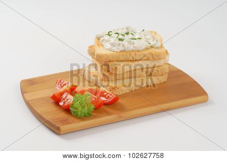 stack of fresh toasts with chives spread on wooden cutting board