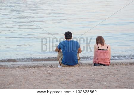 Boy and girl sit on a beach of Adriatic sea in Budva, Montenegro