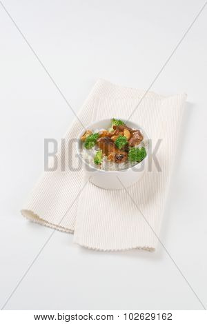 bowl of rice with roasted meat and cashews on white place mat