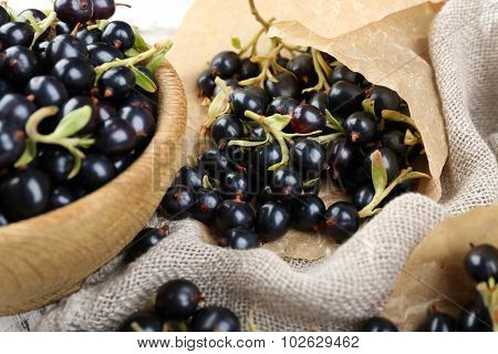 Ripe black currants in wooden bowl on sackcloth, closeup