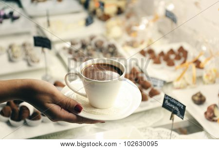 Female hand holding cup of hot chocolate on table background