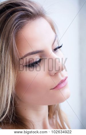 Portrait of a beautiful teenage girl with window in the background