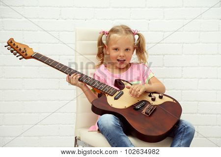 Little girl playing guitar on light background