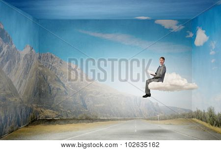 Young businessman floating on cloud with book in hands