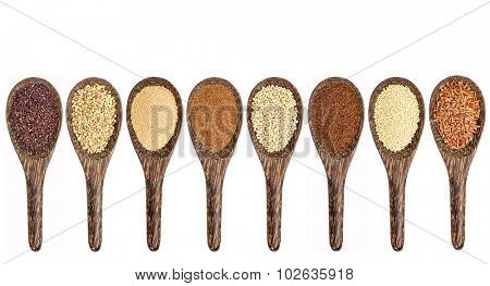a variety of gluten free grains (from left: black quinoa, buckwheat, amaranth, teff, sorghum, kaniwa, millet, and brown rice) - set of wooden spoons isolated on white