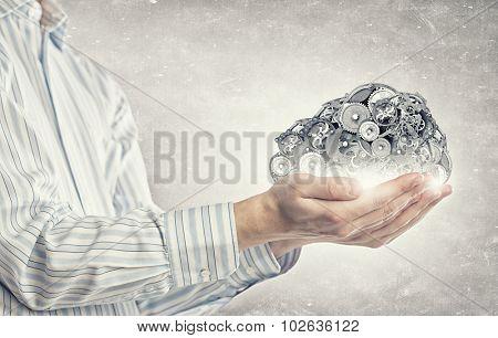 Gears and cogwheels mechanism in hands of businessman