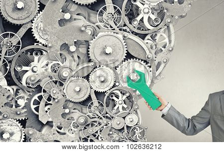 Gears and cogwheels mechanism in hands of businessman