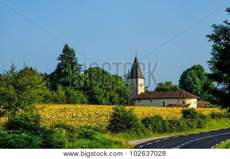 Field of sunflowers and church in France.