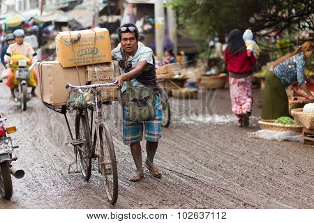 MANDALAY,MYANMAR,JANUARY 17, 2015 : A man is walking, using his bicycle to carry some boxes of food in the muddy street of the Zegyo outdoors market, in Mandalay, Myanmar (Burma).