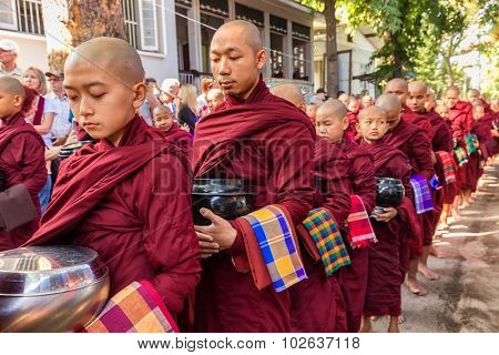 AMARAPURA, MYANMAR, JANUARY 20, 2015 : Young monks are queueing holding their bowls to collect the unique daily meal at noon in the Mahagandayon monastery near Mandalay, Myanmar (Burma).
