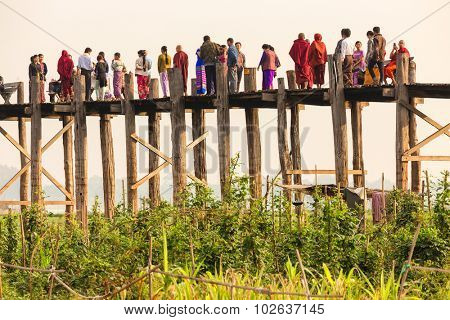 AMARAPURA, MYANMAR, JANUARY 18, 2015 : People are crossing the famous wooden U Bein bridge at dusk in the Amarapura village near Mandalay, Myanmar (Burma).