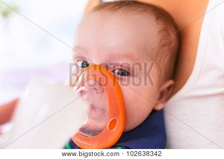 Baby boy taking inhalation therapy by the mask of a nebuliser