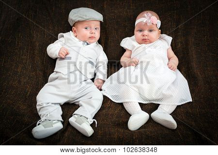 Twin babies dressed up for christening day