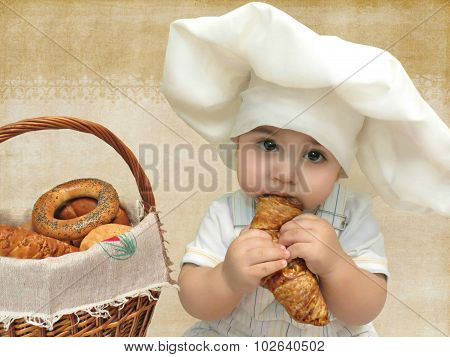 Portrait of a baby boy in a chef's hat with a basket of muffins and bagels eating croissant