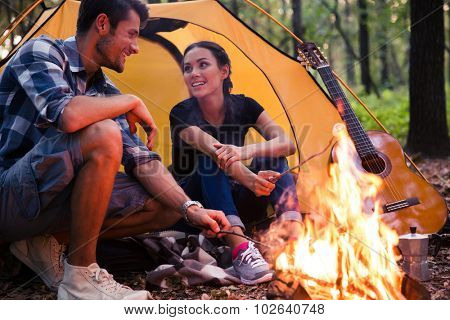 Portrait of a happy couple and bonfire in the forest