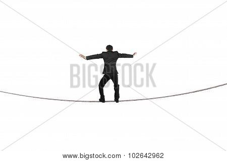 Rear View Of Businessman Balancing On Tightrope