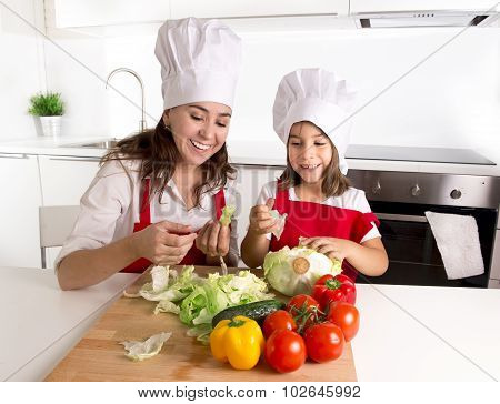 Happy Mother And Little Daughter At Home Kitchen Preparing Salad In Apron And Cook Hat