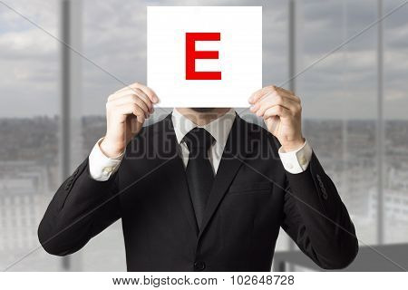 Businessman In Suit Holding Up Sign With Letter E