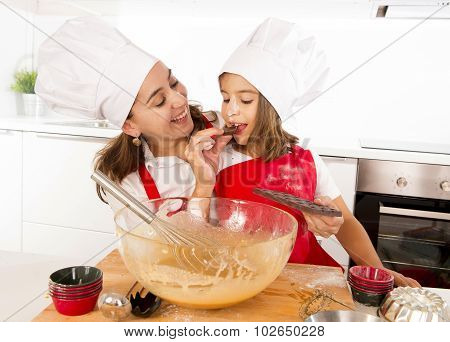Happy Mother Baking With Little Daughter Eating Chocolate Bar Used As Ingredient While Teaching