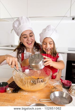 Happy Mother Baking With Little Daughter In Apron And Cook Hat Preparing Dough At Kitchen