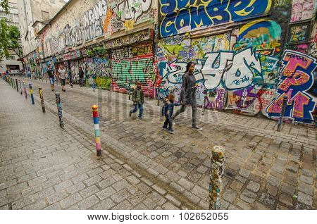 Family passes by dazzling street art on Rue Denoyez in Paris