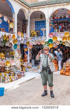 SAFI, MOROCCO, APRIL 6, 2015: Senior tourist takes photos in the pottery souk in Safi, capital of ceramics craft