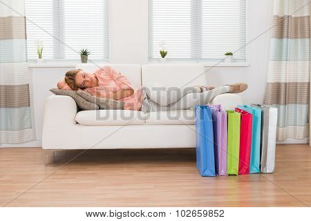 Woman Sleeping With Shopping Bags On Floor
