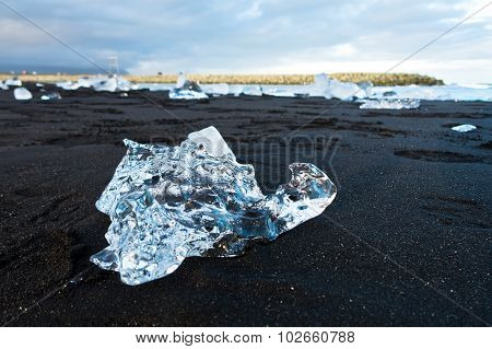 Melting of icebergs at black beach in Jokulsarlon glacier lagoon