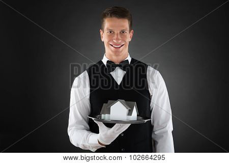 Waiter Holding Tray With Miniature House