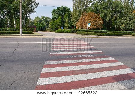 A Red And White Pedestrian Crossing On Asphalt