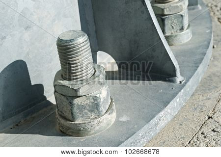 Close up of some larger screws into the base of a metal pillar.