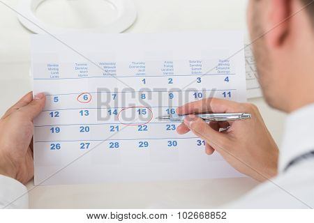 Close-up Of Businessman Marking Date