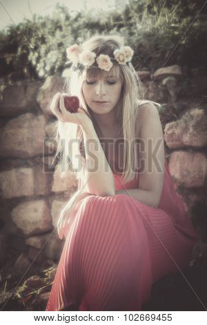 young blonde woman with wreath of flowers hold an apple sit on old stone wall overgrown with grass, wearing long red dress