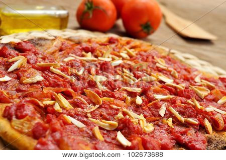 closeup of a coc de tomata, a flat pie with tomato and tuna typical of Valencia, Spain