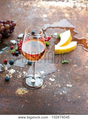 Glass of rose wine with berries, melon, grapes and ice on grunge rusty metal background.