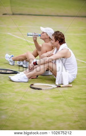 Sport And Fitness Concepts: Happy Caucasian Couple In Tennis Gear Posing On Court During Waterbrake.