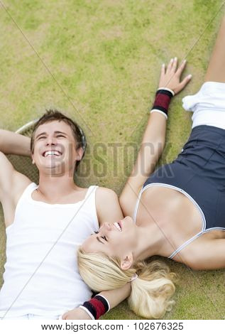 Healthylife Concept: Young Couple Of Tennis Players Resting On Tennis Court And Smiling