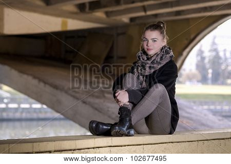 Young Caucasian Teenager Girl Sitting With Her Legs Folded Outdoors. Posing In Trendy Autumn Coat.