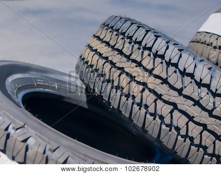 Closeup Of Stack Of Brand New Automobile Black Tyres With Numbers Placed Outdoors