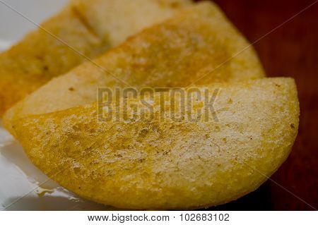 Closeup three perfect empanadas on white plate with wooden surface background