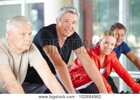 Man in group of seniors in spinning class in a gym