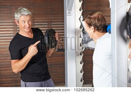 Senior man lifting weights with fitness instructor helping in gym