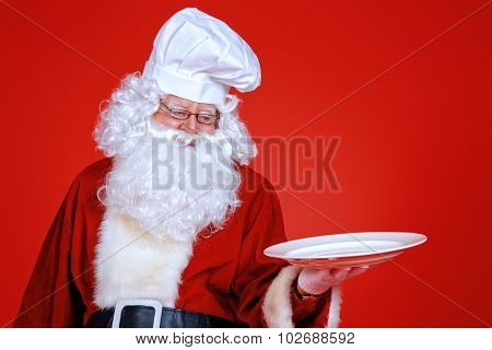 Jolly Santa Claus in a chef's hat holds a plate over festive red background. Copy space. Christmas treats.