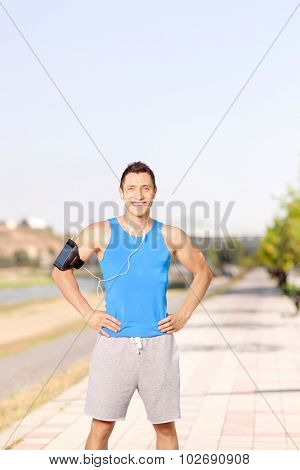 Vertical shot of a young male athlete listening to music on his cell phone and standing on a sidewalk
