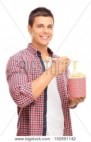 Vertical shot of a joyful young man eating Chinese noodles with sticks and looking at the camera isolated on white background