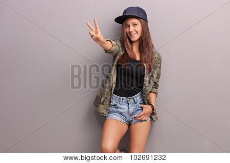 Teenage girl in hip-hop clothes making a peace hand gesture and leaning against a gray wall