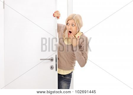 Blond woman peeking from behind a door and making shocked grimace isolated on white background