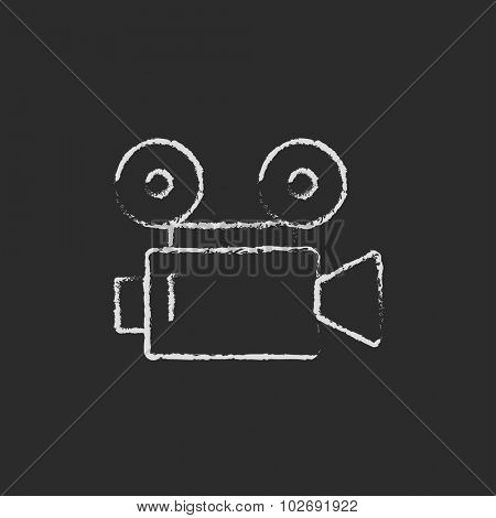 Video camera hand drawn in chalk on a blackboard vector white icon isolated on a black background.