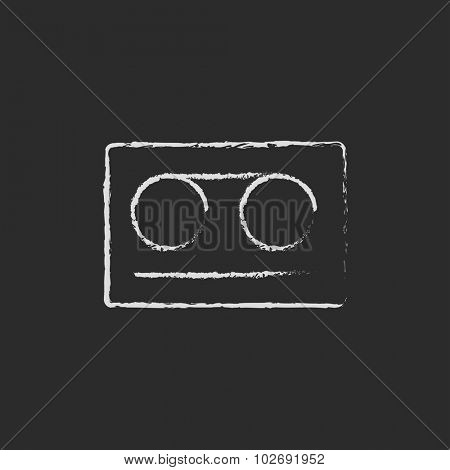 Cassette tape hand drawn in chalk on a blackboard vector white icon isolated on a black background.