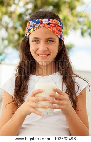 Teenager girl with blue eyes drinking milk glass